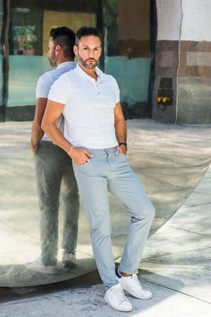 Portrait of Young Man in New York City. Young European Man with beard, little gray hair, wearing white short sleeve shirt, gray pants, white sneakers, standing against metal mirror, looking, thinking.
