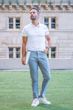 Young European Businessman with beard, little gray hair, wearing white short sleeve shirt, light blue pants, white sneakers, holding laptop computer, standing on green lawn outside in New York City. 版權商用圖片