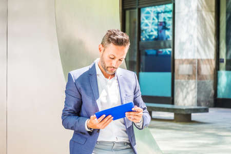 Reading Outside. Young European Man with beard, little gray hair, wearing blue jacket, white shirt, standing by metal silver structure on street in New York City, reading on blue tablet computer. 版權商用圖片
