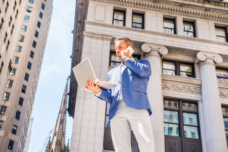 Young European Businessman with beard traveling, working in New York City, wearing blue blazer, gray pants, standing outside old office building, working on laptop computer, talking on cell phone. 版權商用圖片