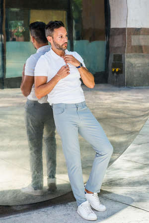 Portrait of Young Man in New York City. Young European Man with beard, little gray hair, wearing white short sleeve shirt, gray pants, white sneakers, standing against metal mirror, looking away,