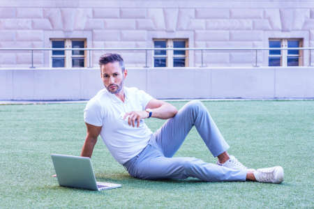 Young European Man with beard, little gray hair, wearing white short sleeve shirt, gray pants, sneakers, sitting on green lawn in New York City, working on laptop computer, looking up, thinking 版權商用圖片