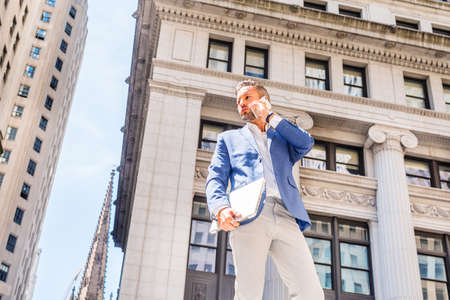 Young European Businessman with beard traveling, working in New York City, wearing blue blazer, gray pants, holding laptop computer, standing outside old office building, calling on cell phone.