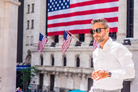 Young European Man with beard traveling in New York in summer, wearing long sleeve white shirt, sunglasses, standing outside old style office building with American flags under sun, looking forward.