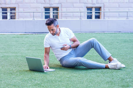 Young European Man with beard, little gray hair, wearing white short sleeve shirt, gray pants, white sneakers, sitting on green lawn in New York City, working on laptop computer, texting on cell phone 版權商用圖片