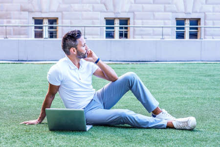 Young European Man with beard, little gray hair, wearing white short sleeve shirt, gray pants, sneakers, sitting on green lawn in New York City, working on laptop computer, looking up, thinking Stock Photo