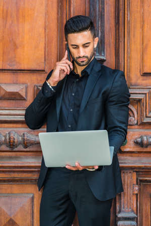 Young East Indian American Businessman with beard working in New York, wearing black suit, black shirt, holding laptop computer, standing by office doorway, talking on cell phone. 版權商用圖片