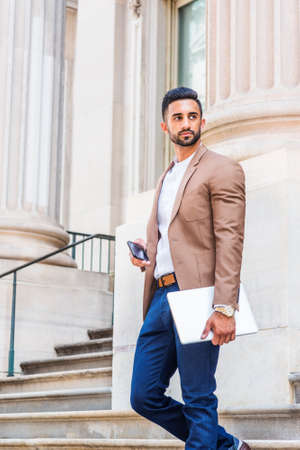 Young East Indian American Businessman with beard working in New York City, wearing brown blazer, white shirt, blue pants, carrying laptop computer, cell phone, standing outside office, looking away. 版權商用圖片