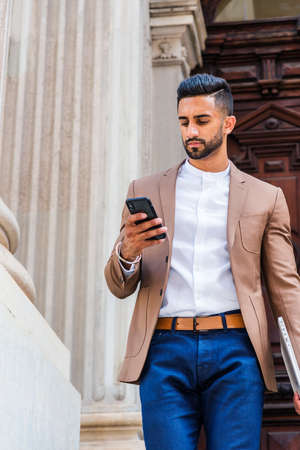 Young East Indian American Man with beard, wearing brown blazer, white round collar shirt, blue pants, carrying laptop computer, standing by old style doorway, looking down, texting on cell phone. 版權商用圖片