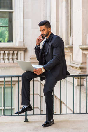Young East Indian American Businessman with beard working in New York, wearing black suit, leather shoes, sitting on railing inside office building, working laptop computer,  talking on cell phone.