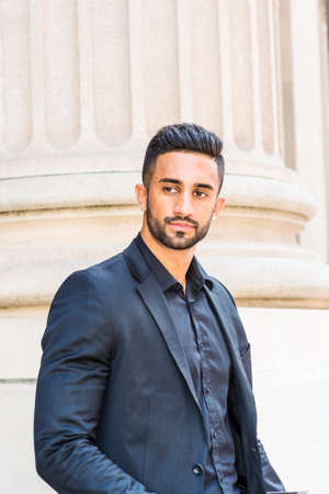 Portrait of Young East Indian American Businessman with beard in New York City, wearing black suit, black shirt, standing by column outside office building, looking away,  thinking.