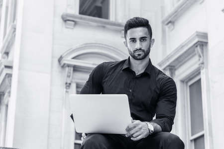 Young East Indian American Man with beard, studying, working in New York City, wearing black shirt, holding laptop computer, sitting outside old style office building, looking up. Black and White. 版權商用圖片