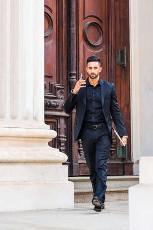 Young East Indian American Businessman traveling, working in New York City, with beard, wearing black suit, carrying laptop computer, walking from old style office doorway, talking on cell phone. 版權商用圖片