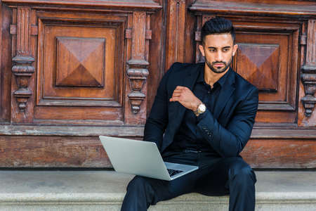 Young East Indian American Businessman with beard working in New York City, wearing black suit, wristwatch, sitting on stairs of office doorway, working on laptop computer, looking away, thinking.
