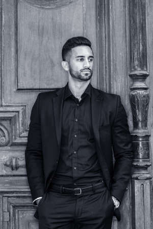 Young East Indian American Businessman with beard, wearing black suit, black shirt, hands in pockets, standing by old style office door in New York City, looking away, thinking. Black and White