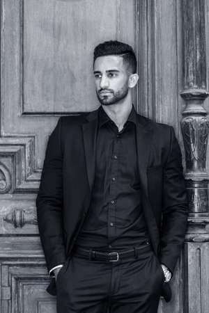 Portrait of Young East Indian American Businessman with beard in New York, wearing black suit, black shirt, hands in pockets, standing by old style office doorway, looking away. Black and White. 版權商用圖片
