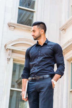Portrait of Young East Indian American Businessman with beard in New York City, wearing black suit, black pants, carrying laptop computer, standing outside old style office building, looking away.