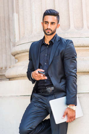 Young East Indian American Businessman with beard working in New York, wearing black suit, carrying laptop computer, standing by column outside office, holding cell phone, looking away,  thinking. 版權商用圖片