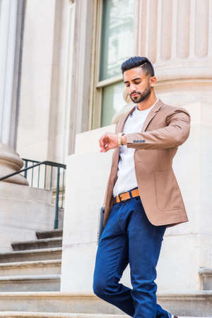 Young East Indian American Businessman with beard working in New York City, wearing brown blazer, blue pants, raising arm, looking down at wristwatch, walking down stairs from office building.