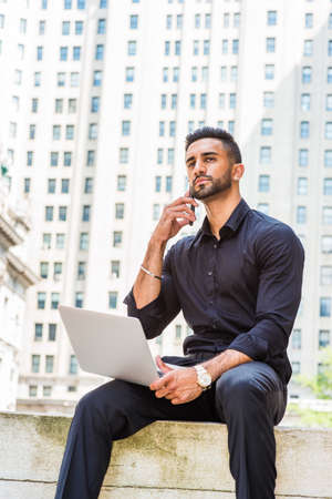 Young East Indian American Businessman with beard traveling, working in New York City, wearing black shirt, holding laptop computer, sitting outside old style office building on street, talking on cell phone.