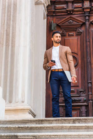 Young East Indian American Man with beard, wearing brown blazer, white round collar shirt, blue pants, carrying laptop computer, holding cell phone, standing in front of old style doorway, looking.