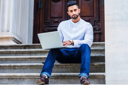 Young East Indian American College Student with beard studying in New York City, wearing white shirt, blue pants, black leather shoes, sitting on stairs outside office, working on laptop computer.