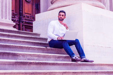 Young East Indian American College Student with beard studying in New York City, wearing white shirt, blue pants, black leather shoes, sitting on stairs, working on laptop computer. Color Filtered.