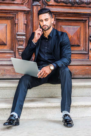 Young East Indian American Man with beard working in New York City, wearing black suit, black shirt, wristwatch, sitting on stairs of office doorway, working on laptop computer, talking on cell phone. 版權商用圖片
