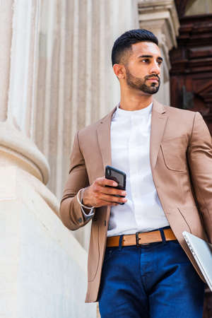 Young East Indian American Man with beard, wearing light brown blazer, white round collar shirt, blue pants, carrying laptop computer, holding cell phone, standing by old style doorway, looking away.