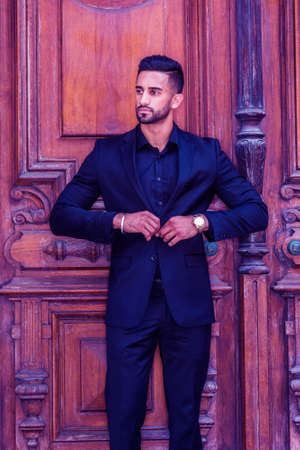 Young East Indian American Businessman with beard, wearing black suit, wristwatch, standing by old style office doorway in New York City, hands in front buttoning clothes, looking away. Color Filtered. 版權商用圖片