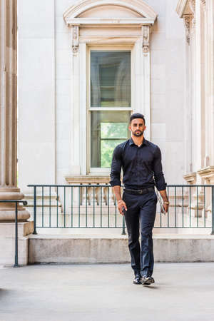 Young East Indian American Man with beard working in New York City, wearing black shirt, black pants, leather shoes, carrying laptop computer, cell phone, walking inside old style office building.