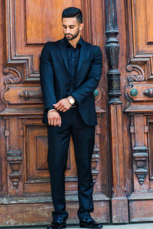 Young East Indian American Businessman with beard, wearing black suit, leather shoes, wristwatch, standing by brown old style office doorway in New York City, hand straightening sleeve.