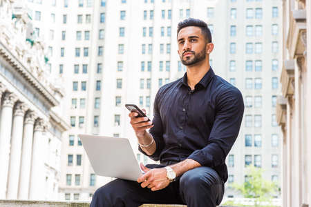 Young East Indian American Businessman with beard traveling, working in New York City, wearing black shirt, holding laptop computer, sitting outside old style office building, texting on cell phone.
