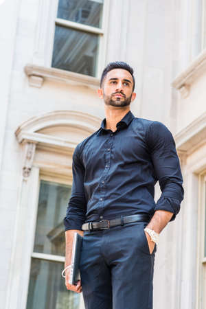 Portrait of Young East Indian American Businessman with beard in New York City, wearing black suit, black pants, carrying laptop computer, standing outside old style office building, looking forward.