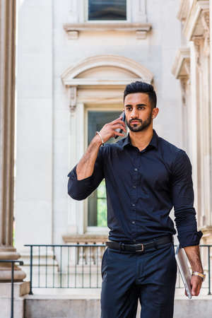 Young East Indian American Man with beard working in New York City, wearing black shirt, black pants, holding laptop computer, walking inside old style office building, talking on cell phone. 版權商用圖片