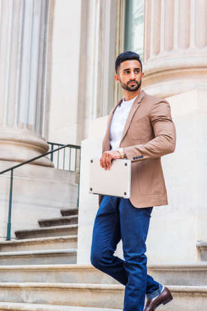 Young East Indian American Man with beard working in New York City, wearing brown blazer, white shirt, blue pants, wristwatch, carrying laptop computer, walking down stairs outside office building.