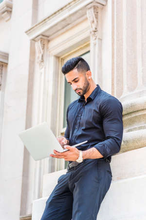 Young East Indian American Businessman with beard working in New York City, wearing black shirt, holding laptop computer, standing outside old style office building, looking down, reading, typing.