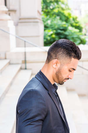 Portrait of Young East Indian American Businessman with beard in New York City, wearing black suit, black shirt, standing on stairs outside office building, looking down, thinking, lost in thought. 版權商用圖片