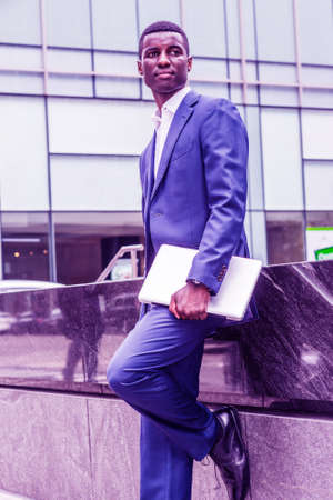 Young African American Businessman traveling in New York City, wearing blue suit, white undershirt, leather shoes, holding laptop computer, standing on street of Midtown of Manhattan, looking away.