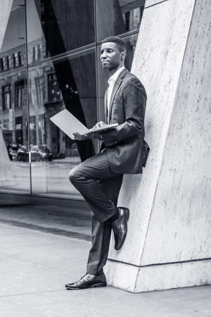 Young African American Businessman working in New York City, wearing suit, white shirt, leather shoes, standing against column on street outside office building, holding laptop computer, thinking.