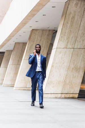 African American businessman traveling, working in New York, wearing blue suit, white undershirt, leather shoes, carrying laptop computer, walking on street outside office building, talking on phone. 版權商用圖片