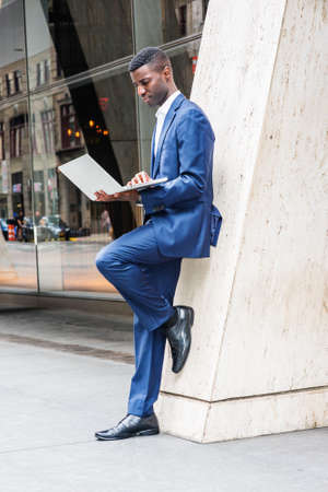 Young African American Businessman working in New York City, wearing blue suit, white shirt, leather shoes, standing against column on street outside office building, reading on laptop computer.