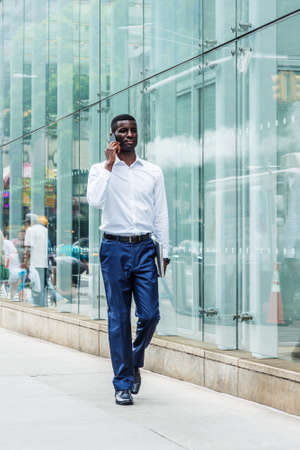 Young African American businessman traveling in New York City, wearing white shirt, blue pants, leather shoes, carrying laptop computer, walking on street by glass wall, talking on cell phone.