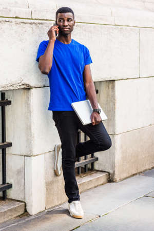 Young African American college student studying in New York City, wearing blue T suit, black pants, white sneakers, holding laptop computer, standing against wall on campus, talking on cell phone. 版權商用圖片