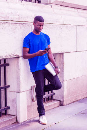 Young African American college student studying in New York City, wearing blue T suit, black pants, sneakers, holding laptop computer, standing against wall outside office building, texting on phone.