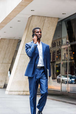Young African American businessman traveling, working in New York City, wearing blue suit, white shirt, walking on street outside office building with glass windows, talking on cell phone. 版權商用圖片