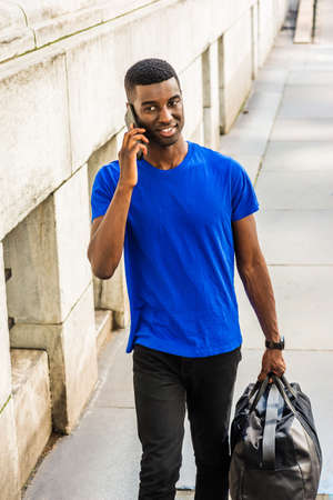 Back to School. Young African American college student studying in New York, wearing blue T suit, black pants,  carrying leather bag, talking on cell phone, walking outside office building on campus.