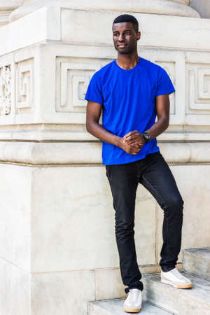 Portrait of Young African American Graduate Student in New York City, wearing blue T shirt, black pants, white sneakers, wristwatch, standing on stairs outside office building on campus.