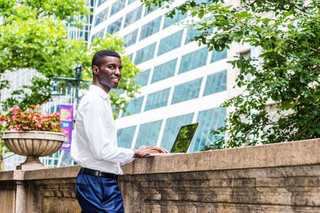 Young African American College Student studying in New York City, wearing white long sleeve shirt, blue pants, standing on campus, working on laptop computer on top of old style fence wall, thinking.