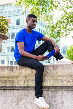Young African American College Student studying in New York City, wearing blue T shirt,  black pants,  white sneakers, sitting on top of wall on campus, holding blue tablet computer, reading, thinking.